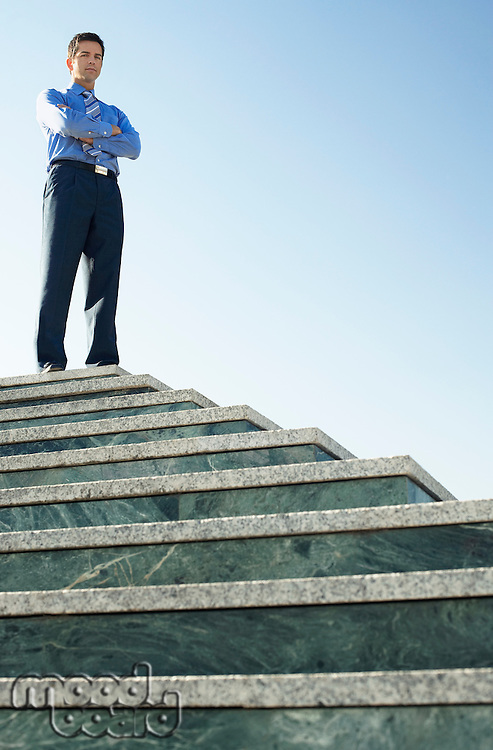 Young Business man standing at top of steps low angle portrait.