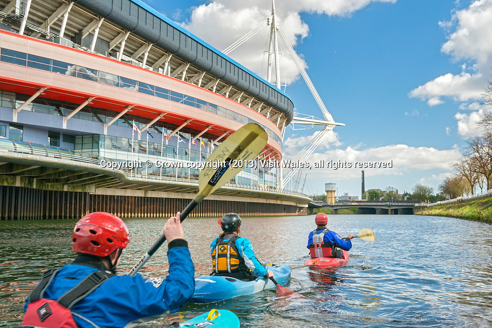 Kayakers passing Millennium Stadium<br /> River Kayaking<br /> River Taff<br /> Cardiff<br /> South<br /> Water Sports<br /> Activities and Sports