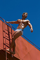male underwear model posing on a ladder outdoors