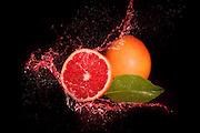 Fresh red grapefruit inside grapefruit juice splash, isolated on black background.