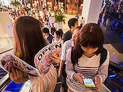 "27 MARCH 2015 - BANGKOK, THAILAND: Shoppers on an escalator in ""EmQuartier,"" a new shopping mall in Bangkok, look at a sale flyer and use their smart phones.  ""EmQuartier"" is across Sukhumvit Rd from Emporium. Both malls have the same corporate owner, The Mall Group, which reportedly spent 20Billion Thai Baht (about $600 million US) on the new mall and renovating the existing Emporium. EmQuartier and Emporium have about 450,000 square meters of retail, several hotels, numerous restaurants, movie theaters and the largest man made waterfall in Southeast Asia. EmQuartier celebrated its grand opening Friday, March 27.   PHOTO BY JACK KURTZ"