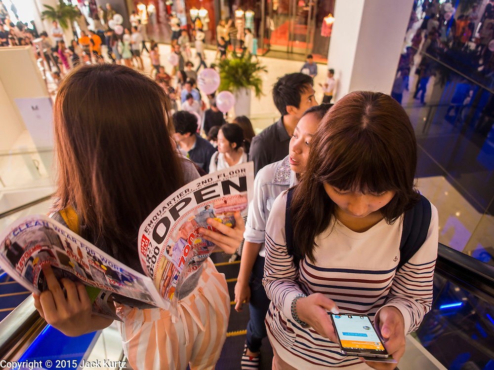"""27 MARCH 2015 - BANGKOK, THAILAND: Shoppers on an escalator in """"EmQuartier,"""" a new shopping mall in Bangkok, look at a sale flyer and use their smart phones.  """"EmQuartier"""" is across Sukhumvit Rd from Emporium. Both malls have the same corporate owner, The Mall Group, which reportedly spent 20Billion Thai Baht (about $600 million US) on the new mall and renovating the existing Emporium. EmQuartier and Emporium have about 450,000 square meters of retail, several hotels, numerous restaurants, movie theaters and the largest man made waterfall in Southeast Asia. EmQuartier celebrated its grand opening Friday, March 27.   PHOTO BY JACK KURTZ"""