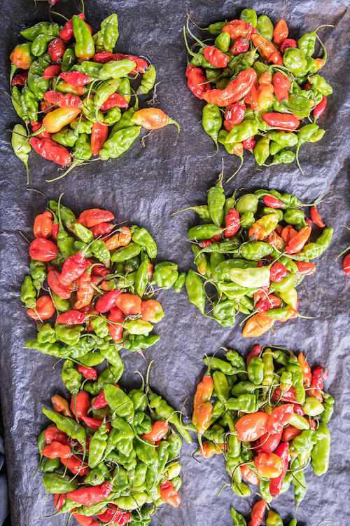 Red and green peppers in groups on a blue cloth Ganta, Liberia