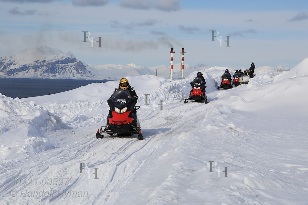 Snowmobile tourists leave Russian coal mining town of Barentsburg amid snow and ice of April; Svalbard, Norway.