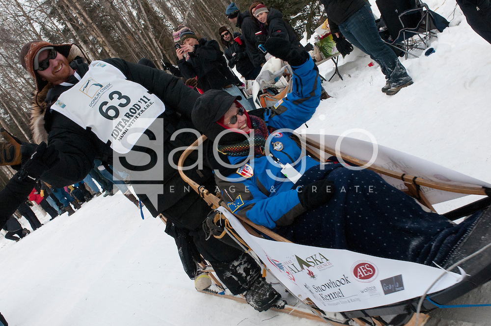 Musher Jerry Sousa and Iditarider Vickey Kunold wave to a crowd of fans along the Chester Creek Trail during the 2011 Iditarod Ceremonial Start.