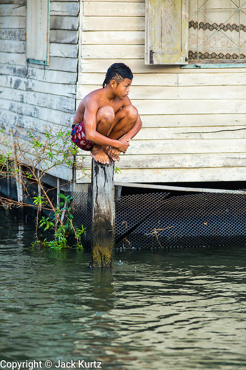 13 JANUARY 2013 - BANGKOK, THAILAND:  A Thai boy rests on a piling while he and his friends were swimming in Khlong Bang Luang in Bangkok. The Bang Luang neighborhood lines Khlong (Canal) Bang Luang in the Thonburi section of Bangkok on the west side of Chao Phraya River. It was established in the late 18th Century by King Taksin the Great after the Burmese sacked the Siamese capital of Ayutthaya. The neighborhood, like most of Thonburi, is relatively undeveloped and still criss crossed by the canals which once made Bangkok famous. It's now a popular day trip from central Bangkok and offers a glimpse into what the city used to be like.     PHOTO BY JACK KURTZ