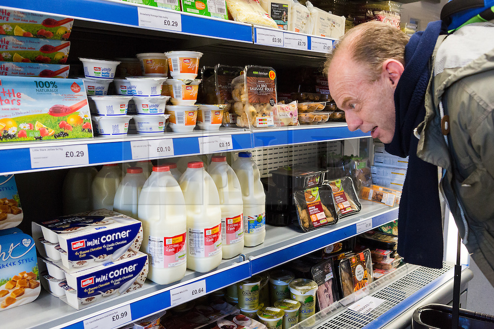 "© Licensed to London News Pictures. 19/12/2014. London, UK. A customer called Robbie looks at milk costing 64p for four pints in the Community Shop. The Community Shop opened this week in Gipsy Hill, South London and is a ""social supermarket"", which sells heavily-discounted surplus food that would otherwise be thrown away. Food is received from retail brands such as Marks & Spencer, Asda, Tesco, Innocent and Muller and many more. The shop works on a membership basis only, serving residents who are on income support and aimed at people who are in work, but low waged and for those working hard to find a job. Photo credit : Vickie Flores/LNP"