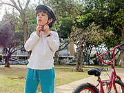 Boy of seven rides his bicycle in an urban park