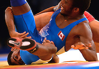 July 31, 2014: Jevon Balfour (blue) of Canada competes against Muhammad Salmon (red) of Pakistan in the 65kg wrestling competition at the Scottish Exhibition Conference Centre, Glasgow during the XX Commonwealth Games in Scotland.