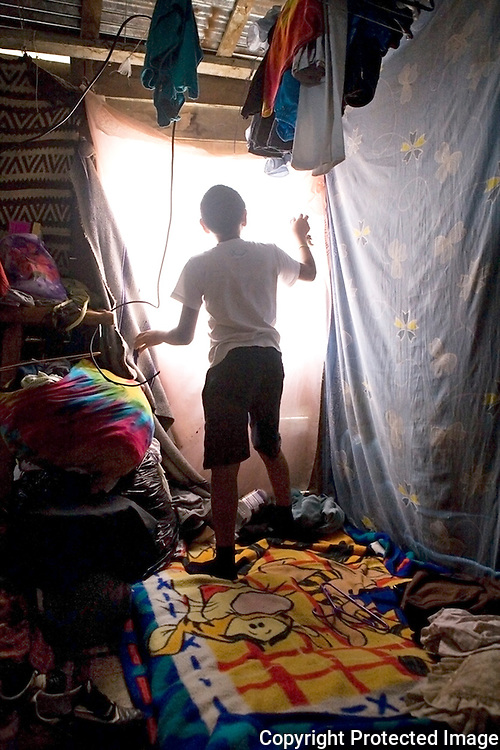 Isreal opening the curatins in the tiny room he shares with his Mother, Father and little brother.