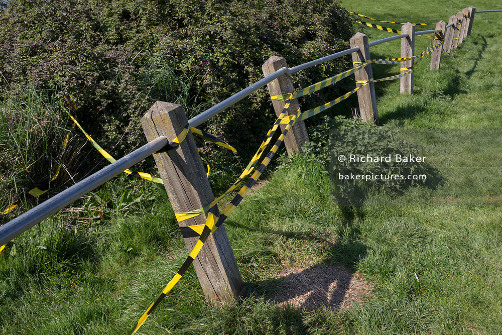 Yellow and black hazard tape stretches along the damaged barrier of a car park at Nailsea Lake, on 21st April 2019, in Nailsea, North Somerset, England