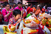 31 JANUARY 2014 - BANGKOK, THAILAND:   A woman prays at the Poh Teck Tung Shrine during Lunar New Year festivities, also know as Tet and Chinese New Year, in Bangkok. This year is the Year of the Horse. Ethnic Chinese make up about 14% of Thailand and Chinese holidays are widely celebrated in Thailand.     PHOTO BY JACK KURTZ