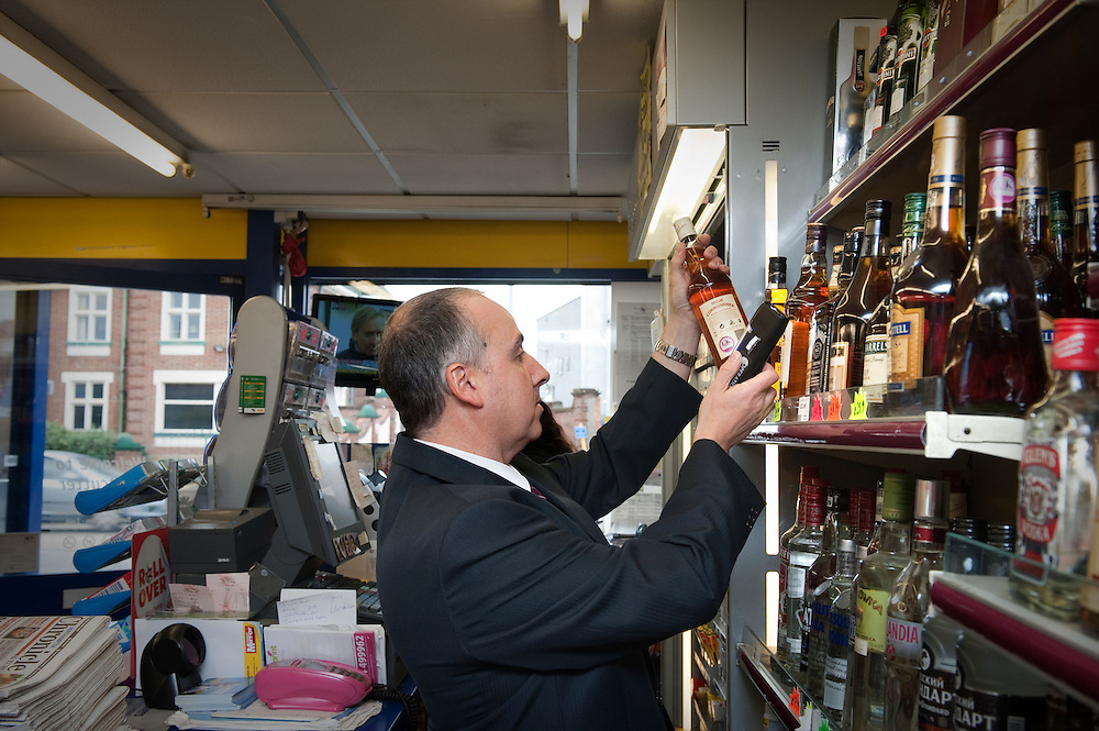 Andy Langford, a Trading Standards Officer from Northampton Trading Standards Authority checking alcohol and cigarettes in a shop, Northampton, Britain.