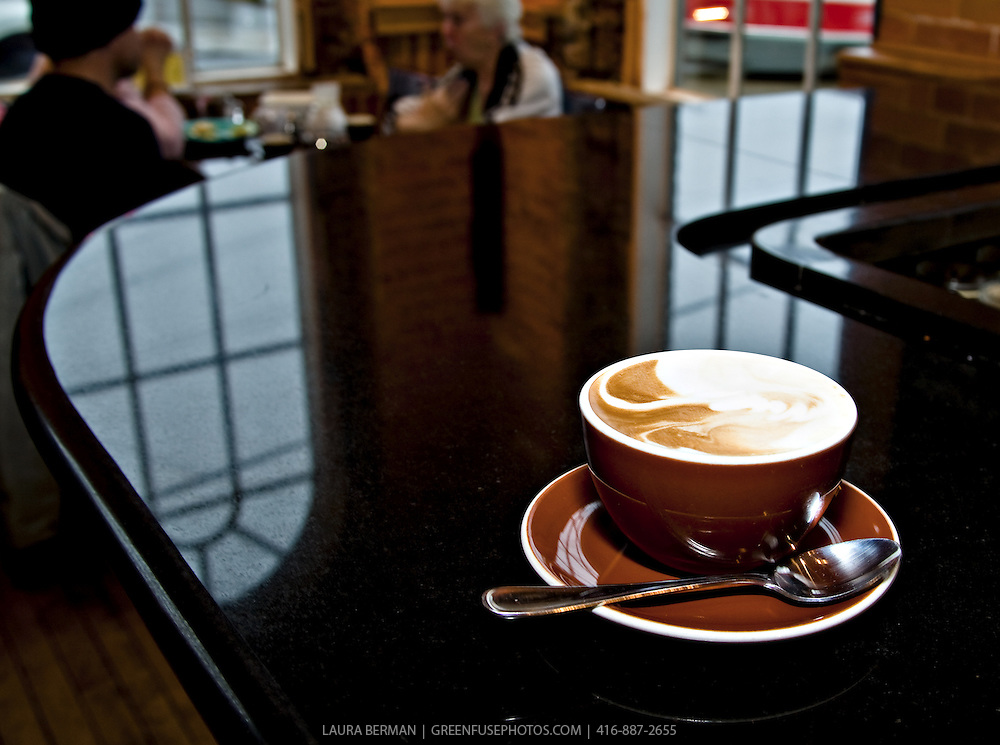 A coffee latte (cafe au lait) in a large brown cup and saucer on a black counter with a window and brick wall in the background