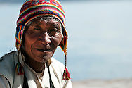 Portrait of a man from the island of Taquile on the Peruvian side of Lake Titicaca.  The men on this island are known for their weaving, and all single men wear a hat made of two solid colors, while married men wear hats of a single color.