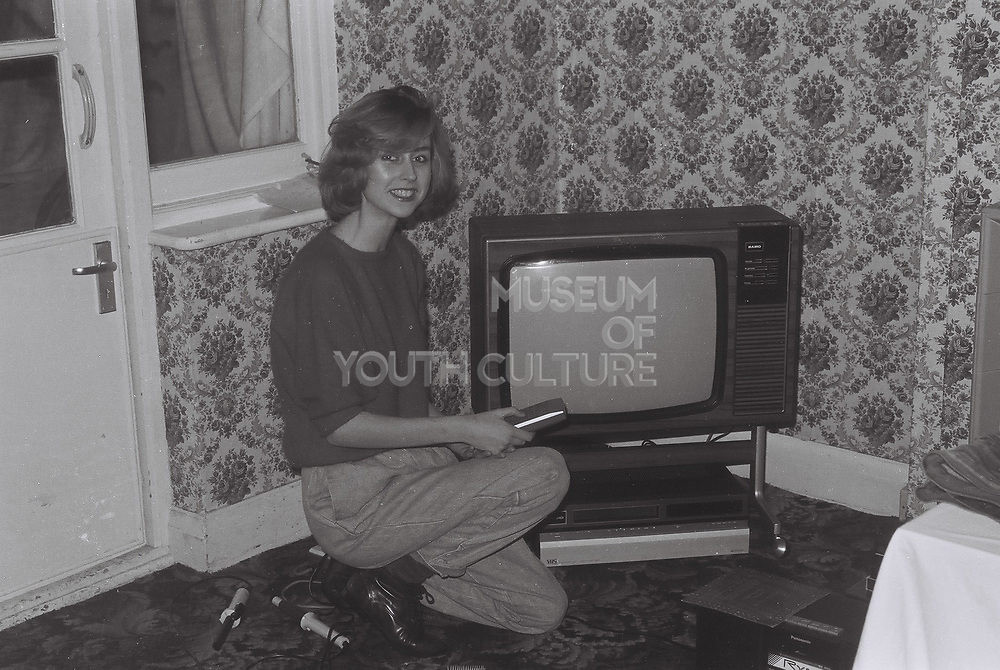Girl posing with rented television and video player, London, UK, 1984