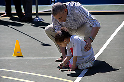 President Barack Obama talks to a little girl playing with her shadow during a basketball clinic at the annual Easter Egg Roll on the South Lawn of the White House, April 6, 2015. (Official White House Photo by Pete Souza)<br /> <br /> This official White House photograph is being made available only for publication by news organizations and/or for personal use printing by the subject(s) of the photograph. The photograph may not be manipulated in any way and may not be used in commercial or political materials, advertisements, emails, products, promotions that in any way suggests approval or endorsement of the President, the First Family, or the White House.
