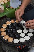 Cooking coconut rice pancakes, Laung Prabang, Laos