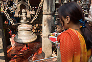 A Hindu girl and child watch a bloody animal sacrifice area under a bell at Durbar Square, Kathmandu, Nepal. Dasain Festival (or Durga Puja) is Nepal's biggest annual festival, a 15-day Hindu family affair with the biggest animal sacrifice of the year. Durga Puja celebrates the victory of the bloodthirsty goddess Durga over the forces of evil personified in the buffalo demon Mahisasura.