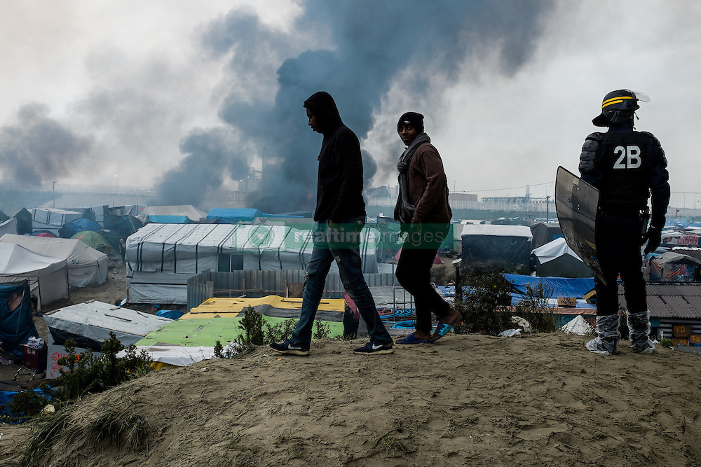 October 26, 2016 - Calais, France - Migrants walk in the Calais Jungle beside a police officer on a sandhill, on October 26, 2016. Huge fires destroyed a mayor part of the refugee camp today. (Credit Image: © Markus Heine/NurPhoto via ZUMA Press)