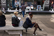 A woman sits with legs crossed in front the Debenhams exterior featuring a male model echoing the same sitting position.