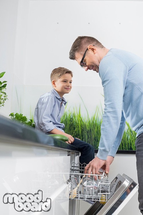 Boy looking at father placing glass in dishwasher at kitchen