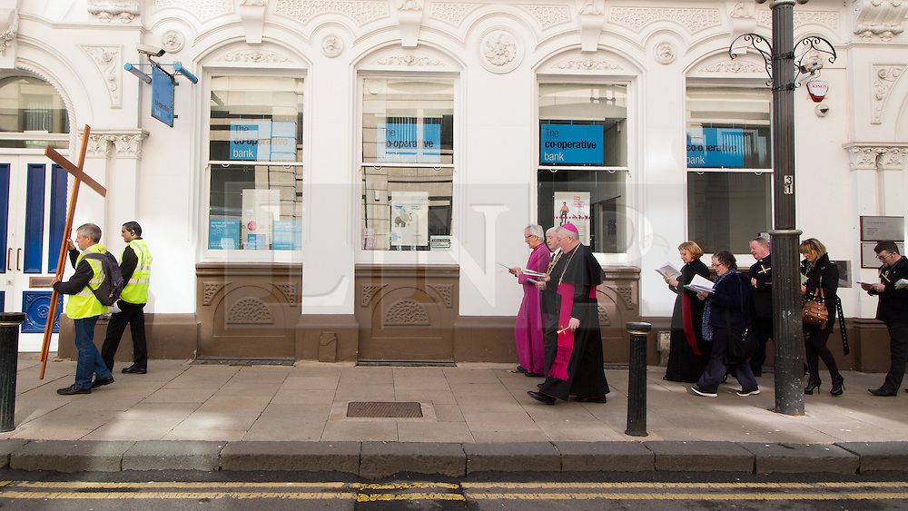 © Licensed to London News Pictures. 25/3/2016. Birmingham, UK. Good Friday Walk of Witness. Churches in Birmingham come together to walk through Birmingham City Centre, visiting Cathedrals and Churches. Pictured, the procession walks along Colmore Row past the Co-operative Bank building. Photo credit : Dave Warren/LNP