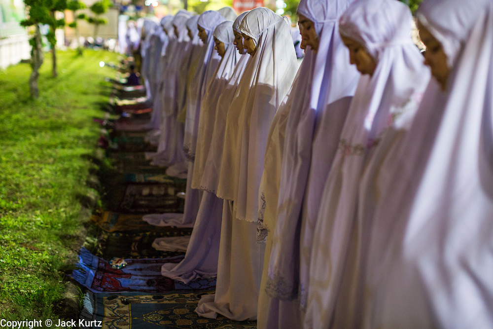 11 JULY 2013 - PATTANI, PATTANI, THAILAND:  Women pray on the public sidewalk in front of the Pattani Central Mosque in Pattani, Thailand, Thursday night for Ramadan services. The mosque is one of the busiest in south Thailand. About 15,000 people attend nightly Ramadan services in the mosque. The crowd is so large it spills out of the mosque and onto the streets around it. Ramadan is the ninth month of the Islamic calendar, and the month in which Muslims believe the Quran was revealed. Muslims believe that the Quran was sent down during this month, thus being prepared for gradual revelation by Jibraeel (Gabriel) to the Prophet Muhammad. The month is spent by Muslims fasting during the daylight hours from dawn to sunset. Fasting during the month of Ramadan is one of the Five Pillars of Islam.     PHOTO BY JACK KURTZ