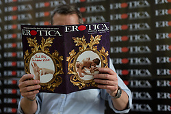 © London News Pictures. 26/10/2013 . London, UK. A man is seen reading the Erotica programme at the Erotica show at Tobacco Dock in East London on 25 October 2013. The three day event runs from 25 October until 27 October and features stalls selling sex toys and clothes and stage shows of exotic dancing. Photo credit : Vickie Flores/LNP