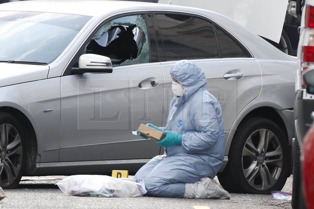 © Licensed to London News Pictures. 13/04/2019. London, UK. A forensics officer gathers evidence next to a car with a smashed window in Holland Park after shots were fired by police near the Ukrainian embassy. Photo credit: Peter Macdiarmid/LNP