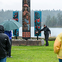 Naturalist Doug Gaultieri interprets the totem poles on the grounds of English Camp, part of San Juan Island National Historical Park, in the San Juan Islands of Washington State.