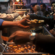 At a popular food stall in old delhi. people buy a famous sweet called Gulab Jamun (goo-laab jaa-moon). It is a popular Indian sweet dish comprised of fried milk balls in a sweet syrup flavoured with cardamom seeds and rosewater or saffron. It may have originated from eastern India (Orissa and Bengal).