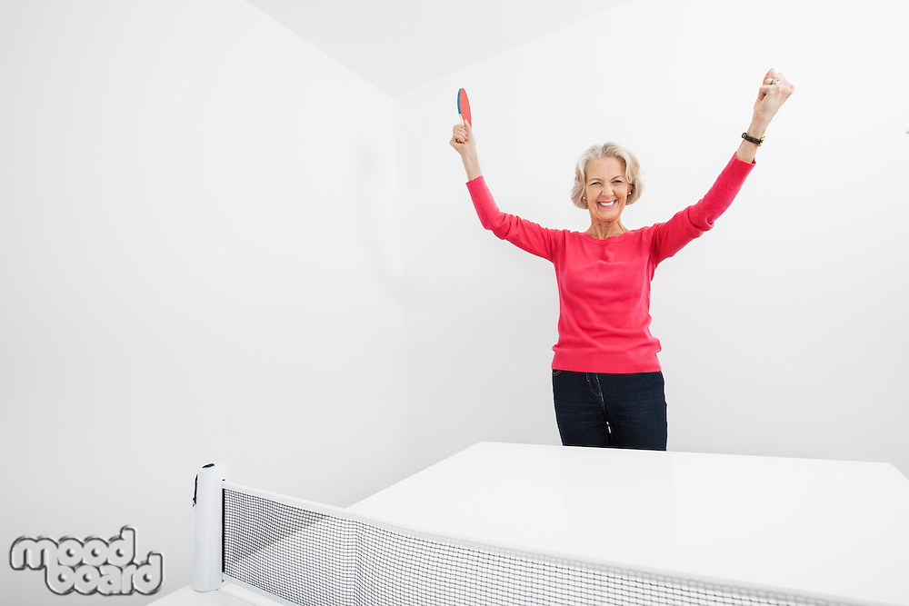 Portrait of senior female table tennis player with arms raised celebrating victory