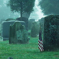 USA, Maryland, Cambridge, American flag by old soldier's gravestone on foggy summer morning