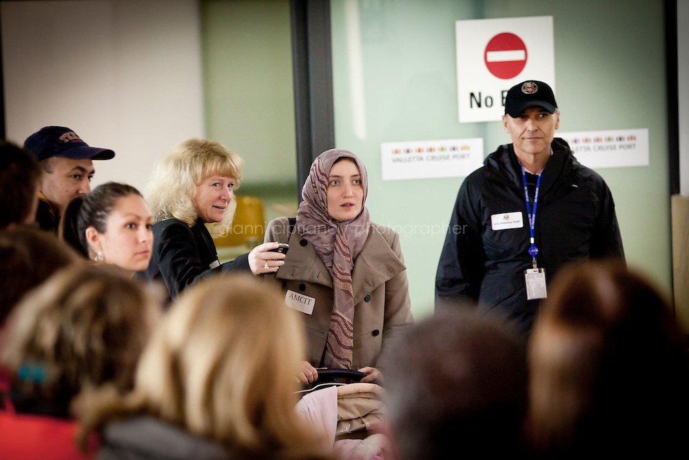 25 February 2011. Valletta, Malta. A US Embassy staff at the Maltese Customs shows a woman arriving from Libya where her husband is waiting for her. A U.S.-chartered ferry evacuated Americans and other foreigners out of Libya on Friday and brought them to the Mediterranean island of Malta. The Maria Dolores ferry, after three days of delays, brought over 300 passengers, including at 167 U.S. citizens, away from Libya where Colonel Gaddafi's forces continue to clash with anti-government demonstrators.<br /> <br /> <br /> &copy;2011 Gianni Cipriano<br /> cell. +1 646 465 2168 (USA)<br /> cell. +39 328 567 7923<br /> gianni@giannicipriano.com<br /> www.giannicipriano.com