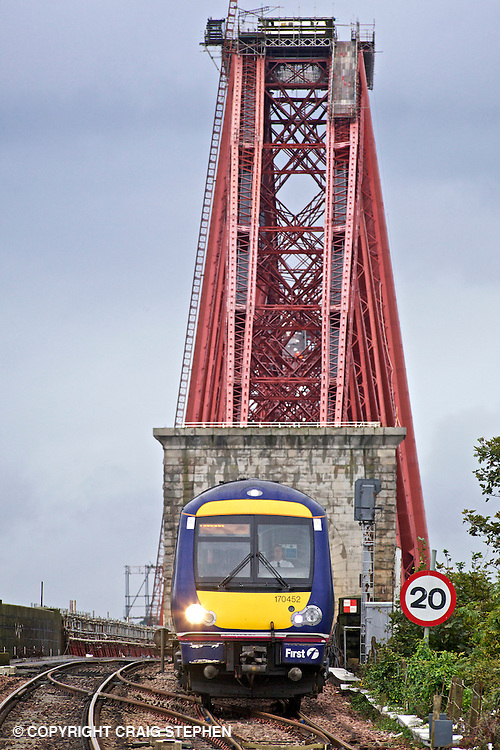 A commuter train crosses the Forth rail bridge in to North Queensferry station, Fife, Scotland