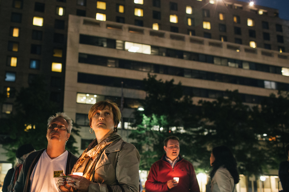 WASHINGTON, DC - SEPTEMBER 16:  Gordon Morris, left, and wife Laura, right, watch as the flags are lowered to half mast during a vigil at Freedom Plaza in Washington, D.C. on Sept. 16, 2013. The vigil, during which organizers called for stricter gun laws, was in remembrance of the more than 10 killed in a shooting at the Navy Yard earlier in the day.   (Photo by Greg Kahn/Getty Images)