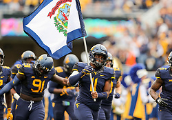 Oct 28, 2017; Morgantown, WV, USA; West Virginia Mountaineers linebacker David Long Jr. (11) holds the West Virginia state flag as they enter the field before their game against the Oklahoma State Cowboys at Milan Puskar Stadium. Mandatory Credit: Ben Queen-USA TODAY Sports