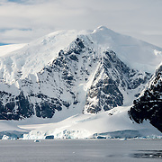 Tall snow and ice-covered mountains rising up from the shore in the Gerlache Strait on the western side of the Antarctic Peninsula.