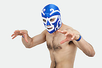 Portrait of a shirtless man in wrestling mask gesturing over gray background