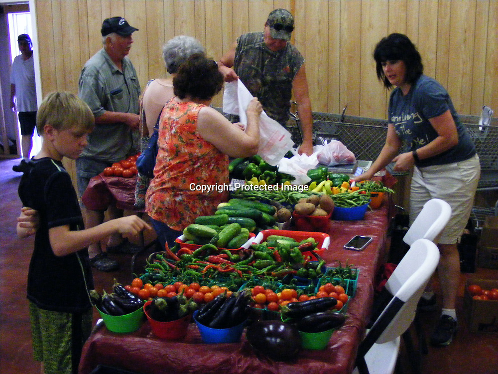 ALICE ORTIZ/BUY AT PHOTOS.MONROECOUNTYJOURNAL.COM<br /> Ginger Autrey, right, of Awtrey Farms in Nettleton sells fresh produce from the farm to waiting customers at Smithville's first Farmacy market on July 1. Twenty vendors with locally grown fresh produce, homemade goodies and a variety of homemade craft items prompted a line of customers waiting for the bell to ring signaling opening time.