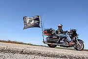 """GENESEE TOWNSHIP, MICHIGAN - APRIL 23: AMA member Mike """"Flagman"""" Bowen from Flushing, Michigan rides his 2007 Harley Davidson Ultra-Classic Electra-Glide down a country road in Genesee Township Sunday, April 23, 2017  near Flint, Michigan. In 2007 Harley Davidson offered a """"Patriot Edition"""" to vets and active duty military. It has the Army logo on the gas tank and American flag on the rear fender. Black with blue and red pin stripping. There was a limited quantity made and Mr. Bowen said he felt lucky to get one.(Photo by Bryan Mitchell)"""