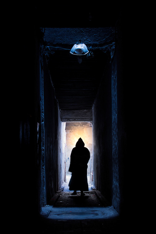 An old man shuffles from darkness into light deep within the ancient walled medina of the city of Fes.