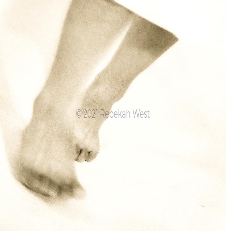 barefoot female feet, edge of white skirt, stepping toward camera, black and white, yellow tone, square format