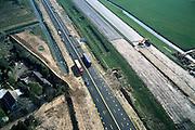 Nederland, Gelderland, Andelst, 04-04-2002; reconstructie Rijksweg A15: in ivm aanleg Betuweroute is de autosnelweg tijdelijk omgelegd (gele wegmarkeringsstrepen op nieuw asfalt); de oude A15 wordt gedeeltelijk gesloopt en krijgt nieuwe op- en afritten; de Betuweroute komt uiteindelijke op de plaats van de tijdelijke weg; aanleg wegen, verkeer en vervoer .Deel van een serie over Betuweroute / infrastructuur.<br /> luchtfoto (toeslag), aerial photo (additional fee)<br /> photo/foto Siebe Swart