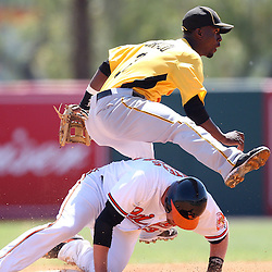 March 14, 2011; Sarasota, FL, USA; Pittsburgh Pirates shortstop Pedro Ciriaco (3) leaps over Baltimore Orioles catcher Matt Wieters (32) after throwing to first base to complete a double play during a spring training exhibition game at Ed Smith Stadium.   Mandatory Credit: Derick E. Hingle