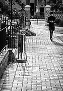 Street photography composition of a student passing the Lieber College on the Horseshoe on the campus of the University of South Carolina in Columbia