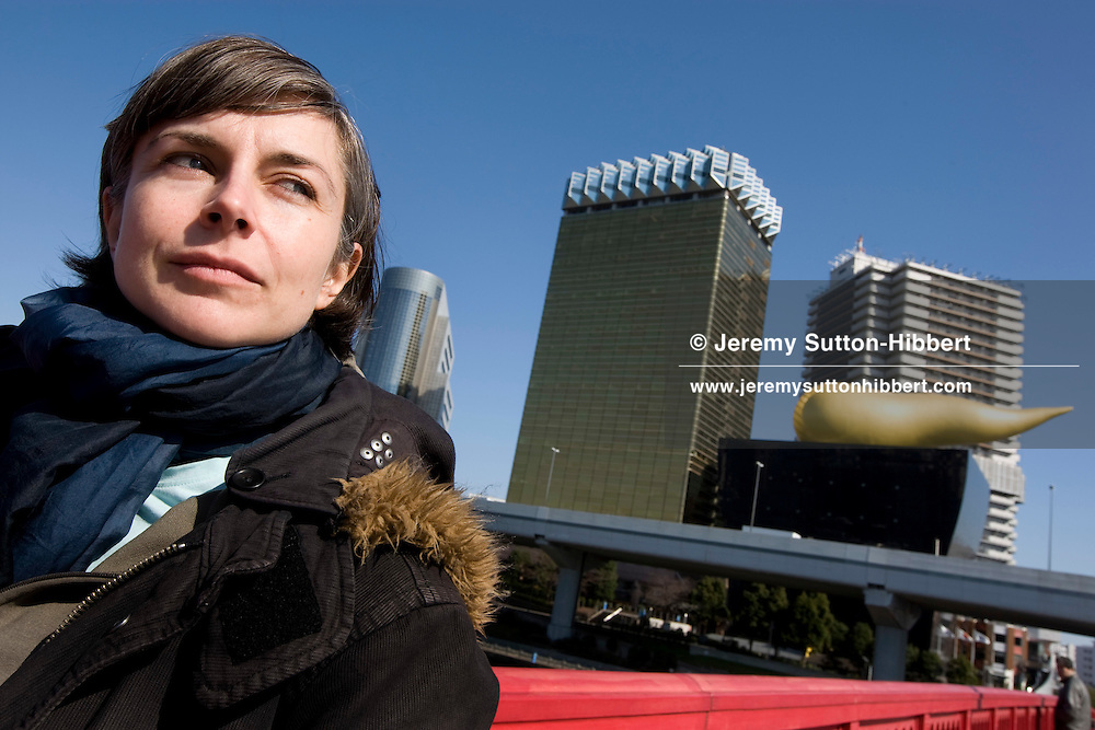 The Times journalist Kathleen Wyatt stands in front of the gold flame shaped Asahi beer company 'Super Dry Hall'- designed by French architect Philippe Starck, and standing beside the Sumida river, in the Asakusa district, Tokyo, Japan, Monday 3rd March 2009.