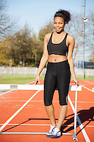 Happy young female athlete standing against hurdle at running track