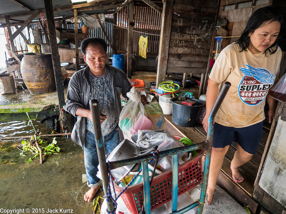 05 OCTOBER 2015 - BANGKOK, THAILAND: A worker, left, packs out a resident's (right)  posessions on moving day in the Wat Kalayanamit neighborhood. The people moving were being evicted from their homes. Fifty-four homes around Wat Kalayanamit, a historic Buddhist temple on the Chao Phraya River in the Thonburi section of Bangkok, are being razed and the residents evicted to make way for new development at the temple. The abbot of the temple said he was evicting the residents, who have lived on the temple grounds for generations, because their homes are unsafe and because he wants to improve the temple grounds. The evictions are a part of a Bangkok trend, especially along the Chao Phraya River and BTS light rail lines. Low income people are being evicted from their long time homes to make way for urban renewal.        PHOTO BY JACK KURTZ